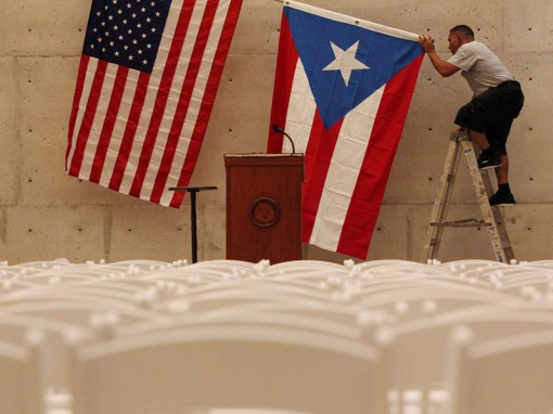 A worker takes off the U.S and Puerto Rican flag after a rally of U.S. Democratic presidential candidate Bernie Sanders in San Juan